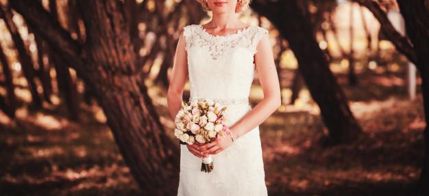 bride-white-dress-holding-bouquet-flowers_84738-2490