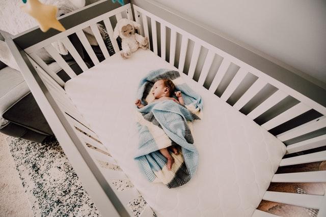 Dieťa zabalené v modrej deke, ležiace v detskej postieľke.jpg