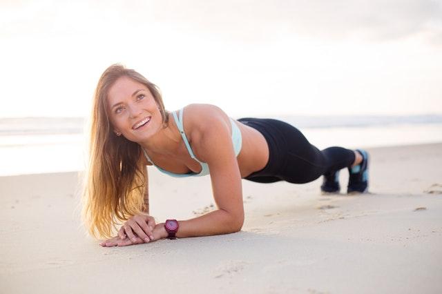 Žena v športovom oblečení cvičí jogu na pláži.jpg