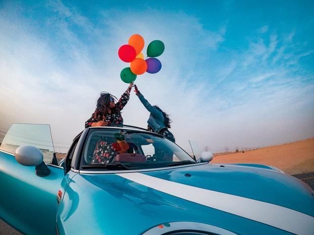 Ženy sedia v modrom aute a v rukách držia zväzok farebných balónov.jpg