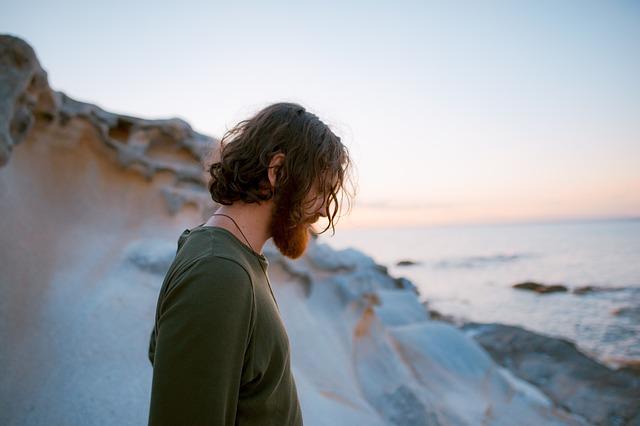 Muž v zelenom tričku s dlhými vlasmi stojí na útese.jpg